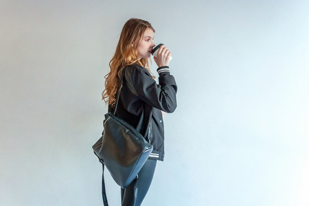 Young teenage girl in leather jacket against white wall, holding paper cup and drinking coffee. Casual daily lifestyle. Pretty sexy fashion sensual woman dressed in hipster rock style outfit