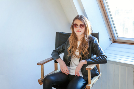 Young teenage girl in leather jacket sitting on modern chair posing in bright light room against white wall background window. Pretty sexy fashion sensual woman dressed in hipster rock style outfit