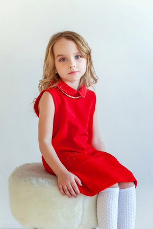 Sweet happy little girl in red dress sitting on chair against white wall background in bright room 写真素材