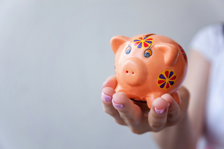 Woman hand hold pink piggy bank. Saving investment budget wealth business retirement concept