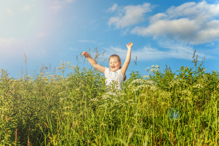 Happy cute little girl running on the grass in the park. Happiness. Healthy preschool children summer activity. Kids playing outdoors