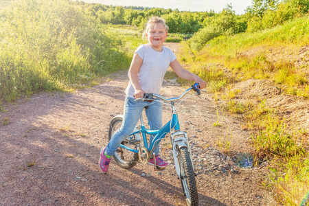 Happy child riding bike. Young girl on bicycle in sunny summer park. Healthy school children summer activity. Kids playing and cycling outdoors. Little girl learns to keep balance while riding bicycle