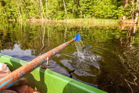 Closeup of oar paddle from row boat moving in water on green lake with ripples. Camping tourism relax trip active lifestyle adventure concept