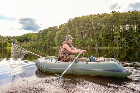 Fisherman with fishing rods is fishing in a rubber boat against background of beautiful nature and lake or river. Camping tourism relax trip active lifestyle adventure concept