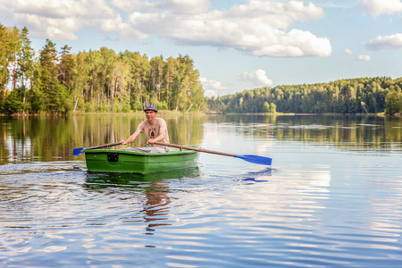 Fisherman with fishing rods is fishing in a wooden boat against background of beautiful nature and lake or river. Camping tourism relax trip active lifestyle adventure concept