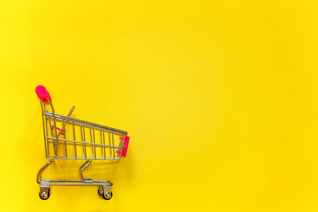 Small supermarket grocery push cart for shopping toy with wheels and pink plastic elements on yellow colourful trendy modern fashion background. Concept of shopping. Copy space for advertisement