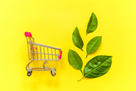 Small shopping trolley cart toy with green leaves on yellow colourful trendy modern fashion background. Ecology eco products health food vegan vegetarian shopping concept