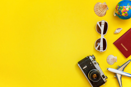 Flat Lay with plane, vintage camera, passport, globe, sunglasses and shell on yellow colourful trendy modern fashion background. Vacation travel summer weekend sea adventure trip concept