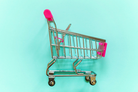 Small supermarket grocery push cart for shopping toy with wheels and pink plastic elements on blue pastel color paper geometric flat lay background. Concept of shopping. Copy space for advertisement