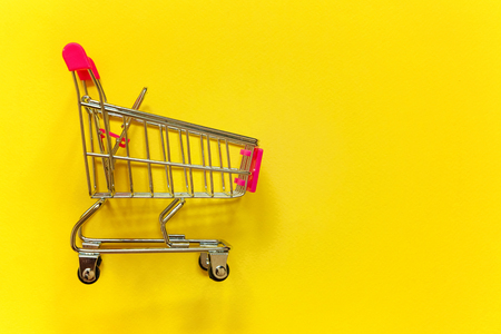 Small supermarket grocery push cart for shopping toy with wheels and pink plastic elements on yellow colourful trendy modern fashion background.