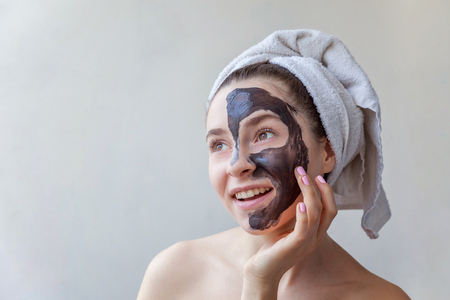 Beauty portrait of a smiling brunette woman in a towel on the head applying black nourishing mask on face on white background isolated. Skincare cleansing spa relax cosmetics concept