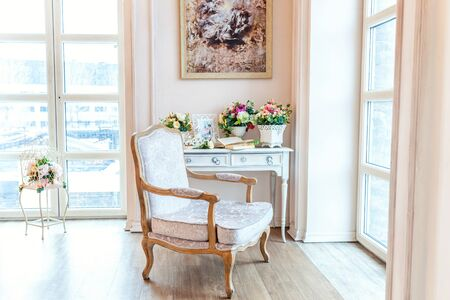 Beautiful luxury classic white bright clean interior bedroom in baroque style with large window, armchair and flower composition