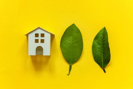 Miniature toy model house with green leaves on yellow colourful trendy backgdrop. Eco Village, abstract environmental background. Real estate mortgage property insurance dream home ecology concept
