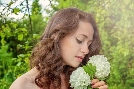 Beautiful young brunette girl with perfect skin holding white flower in hand on park or garden green background. Beauty nature skincare eco organic cosmetic ecology pure health concept Standard-Bild