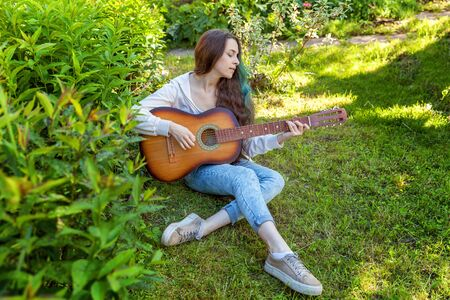 Young hipster woman sitting in grass and playing guitar on park or garden