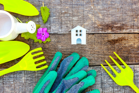 Flat Lay with gardening tools, watering can, shovel, spade, rake, glove, flowers and toy house on rustic wooden background. Spring or summer in garden, eco, nature, farm, horticulture hobby concept