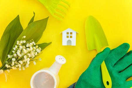Flat Lay gardening tools, watering can, shovel, rake, glove, flowers and toy house on yellow colourful trendy background. Spring or summer in garden, eco, nature, farm, horticulture hobby concept