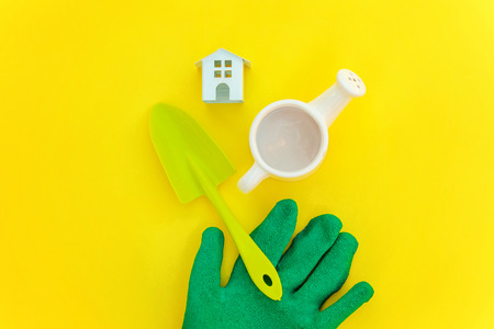 Flat Lay gardening tools, watering can, shovel, rake, glove and toy house on yellow colourful trendy background. Spring or summer in garden, eco, nature, farm, horticulture hobby concept