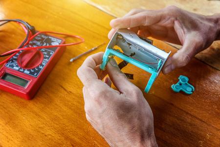 Man hands fixing modern vaporizer e-cig gadget to vape e-liquid. Maintenance of electronic equipment mech mod vaping device. Vaper device repair service