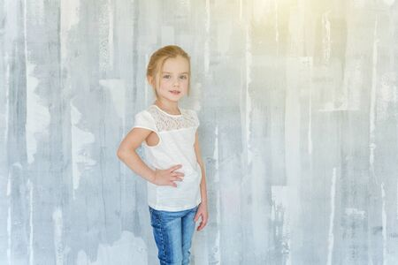 Sweet happy little girl in blank white t-shirt standing against grey textured wall background. Childhood, schoolchildren, youth, relax concept