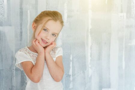Sweet happy little girl in blank white t-shirt standing against grey textured wall background Childhood, schoolchildren, youth, relax concept Фото со стока