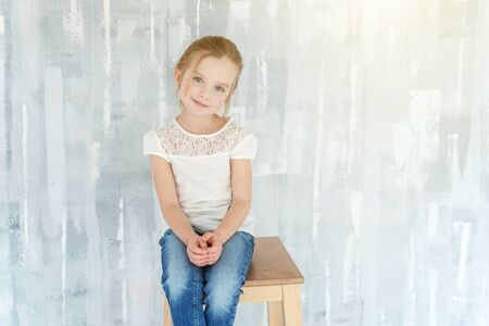 Sweet happy little girl in blank white t-shirt sitting on chair against grey textured wall background Childhood, schoolchildren, youth, relax concept