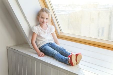 Little cute sweet smiling girl in jeans and white T-shirt sitting on the window sill in bright light living room at home and thinking Childhood, schoolchildren, youth, relax concept 写真素材