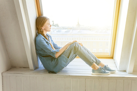 Young happy cute teenage girl in jeans, denim jacket and white T-shirt sitting sitting on the window sill in bright light living room at home and thinking Childhood, schoolchildren, youth, relax conce 写真素材