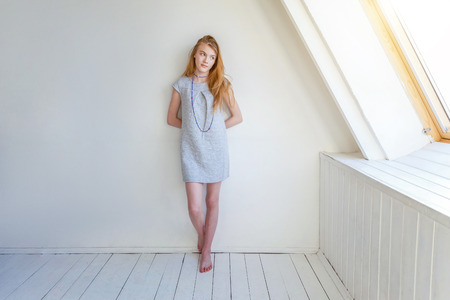 Happy teenage girl smiling. Closeup portrait young happy positive woman in grey dress at home in bright room against white wall. European woman. Positive human emotion facial expression body language