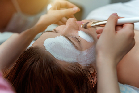 Close-up of young beauty brunette woman getting face treatment with white nourishing creme in spa salon. Face massage. Spa skin and body care. Skincare cleansing cosmetic spa relax concept 写真素材
