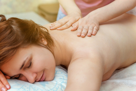 Close-up of young beauty brunette woman getting body back massage treatment in spa salon. Spa skin and body care. Skincare cleansing cosmetic health spa relax pleasure concept