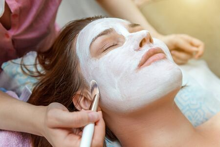 Close-up of young beauty brunette woman getting face treatment with white nourishing creme in spa salon. Face massage. Spa skin and body care. Skincare cleansing cosmetic spa relax concept 版權商用圖片