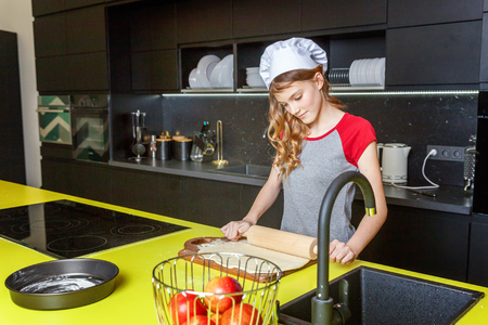 Teenage girl with chef hat, rolling pin preparing dough, bake homemade holiday apple pie in kitchen. Young woman cooking healthy food at home and having fun. Food, healthy eating, household concept