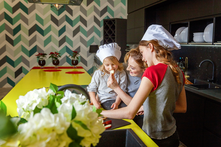 Happy family in kitchen. Mother and two children preparing dough, bake apple pie. Mom and daughters cooking healthy food at home and having fun. Household, teamwork helping, maternity concept 写真素材