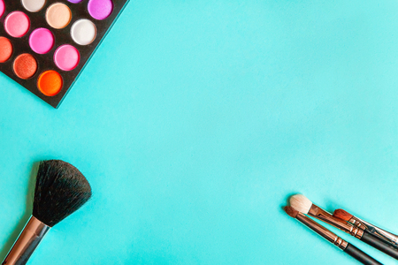 Tools for makeup and cosmetics different shades of eyeshadow palette and make up brush on trendy colorful blue pastel background. Top view flat lay and picturesque