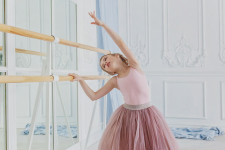 Young classical ballet dancer girl in dance class. Beautiful graceful ballerina practice ballet positions in pink tutu skirt near large mirror in white light hall