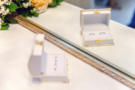 Two beautiful wedding rings on white jewelry box on light background. Declaration of love Wedding card Valentines Day greeting. Wedding rings. Wedding day details 写真素材