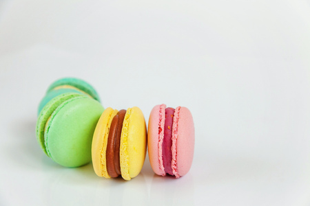 Sweet almond colorful pink, biue, yellow, green macaron or macaroon dessert cake isolated on white background. French sweet cookie. Minimal food bakery concept. Flat lay, top view, copy space 写真素材