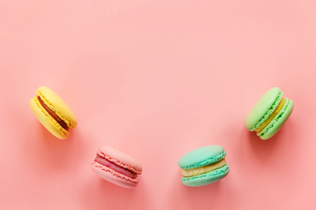 Sweet almond colorful pink biue yellow green macaron or macaroon dessert cake isolated on trendy pink pastel background. French sweet cookie. Minimal food bakery concept. Flat lay top view copy space