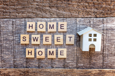 Miniature toy model house with inscription HOME SWEET HOME letters word on wooden backdrop. Eco Village, abstract environmental background. Real estate mortgage property insurance ecology concept Stok Fotoğraf