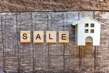 Miniature toy model house with inscription SALE letters word on wooden backdrop. Eco Village, abstract environmental background. Real estate mortgage property insurance sweet home ecology sale concept
