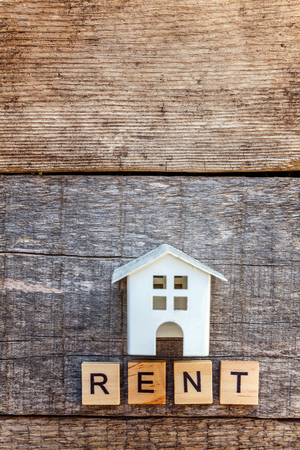 Miniature toy model house with inscription RENT letters word on wooden backdrop. Eco Village, abstract environmental background. Real estate mortgage property insurance sweet home ecology rent concept