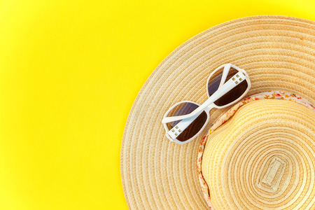 Flat Lay with sunglasses and striped retro hat on yellow colourful trendy modern fashion background. Vacation travel summer weekend sea adventure trip concept Stok Fotoğraf