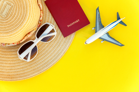 Flat Lay with hat, plane, passport and sunglasses on yellow colourful trendy modern fashion background. Vacation travel summer weekend sea adventure trip concept Stok Fotoğraf