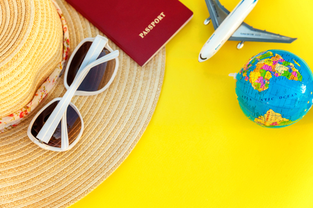 Flat Lay with hat, plane, passport, globe and sunglasses on yellow colourful trendy modern fashion background. Vacation travel summer weekend sea adventure trip concept