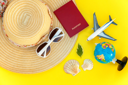 Flat Lay with hat, plane, passport, globe, sunglasses and shell on yellow colourful trendy modern fashion background. Vacation travel summer weekend sea adventure trip concept