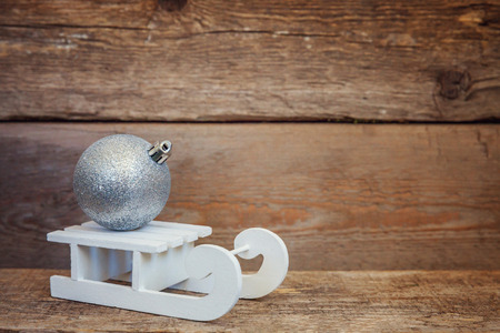 Christmas New Year composition winter objects balls and sled on old shabby rustic wooden background. Xmas holiday december decoration copy space. Time for celebration