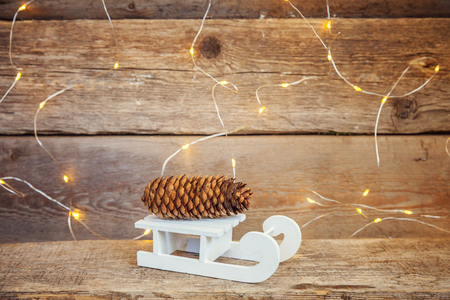 Christmas New Year composition winter objects garland lights pine cone and sled on old shabby rustic wooden background. Xmas holiday december decoration copy space. Time for celebration