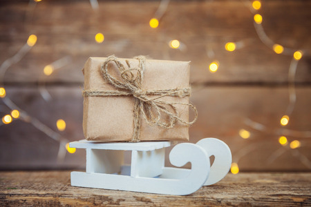 Christmas New Year composition winter objects garland lights gift box and sled on old shabby rustic wooden background. Xmas holiday december decoration copy space. Time for celebration Stok Fotoğraf
