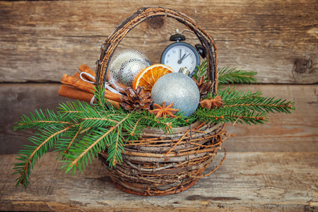 Christmas New Year composition winter objects fir branch basket pine cones balls cinnamon sticks alarm clock on old shabby rustic wooden background. Xmas holiday december decoration copy space